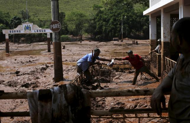 Men take out a bag from a house flooded with mud after a dam owned by Vale SA and BHP Billiton Ltd burst, in Barra Longa, Brazil, November 7, 2015.  REUTERS/Ricardo Moraes
