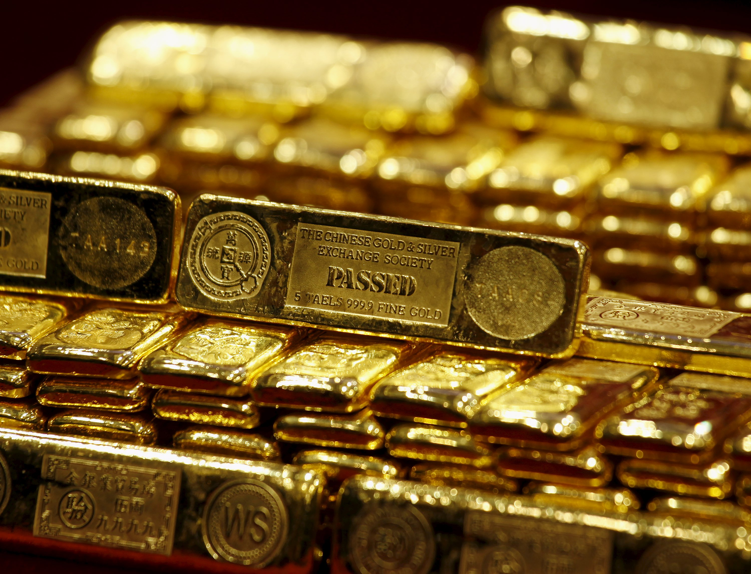 New five-tael 24K gold bars, issued by the Chinese Gold and Silver Exchange Society, Hong Kong's major gold and silver exchange, are introduced during the first trading day after the Chinese New Year holidays in Hong Kong in this February 14, 2013 file photo.  REUTERS/Bobby Yip/Files