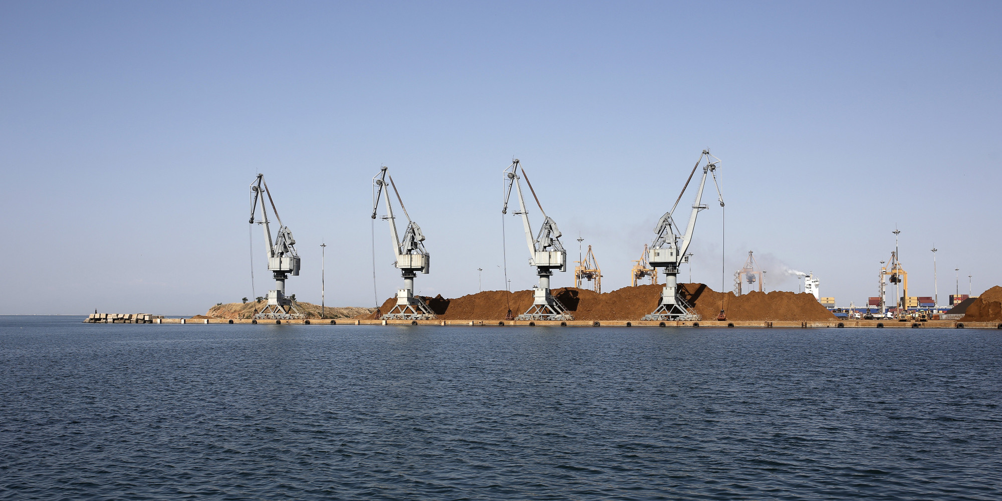 Shipping cranes stand beside supplies of unprocessed nickel ore on the dockside at Thessaloniki port, operated by Thessaloniki Port Authority SA, in Thessaloniki, Greece, on Thursday, July 16, 2015. A.P. Moeller-Maersk A/S wants to buy Greece's two biggest ports after Prime Minister Alexis Tsipras put them up for sale in his proposal of budget-enhancing measures submitted to creditors. Photographer: Konstantinos Tsakalidis/Bloomberg via Getty Images